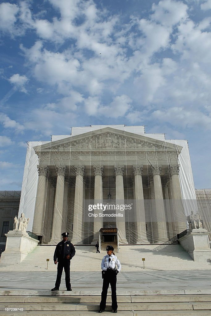 U.S. Supreme Court Police officers stand on the steps in front of the court building November 30, 2012 in Washington, DC. With the Supreme Court building draped in a photo-realistic sheet during a repair and preservation project, the justices met today to consider hearing several cases dealing with the rights of gay couples who are married, want to get married or are in domestic partnerships.