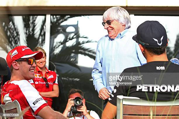 F1 supremo Bernie Ecclestone chats with Sebastian Vettel of Germany and Ferrari and Lewis Hamilton of Great Britain and Mercedes GP during previews...