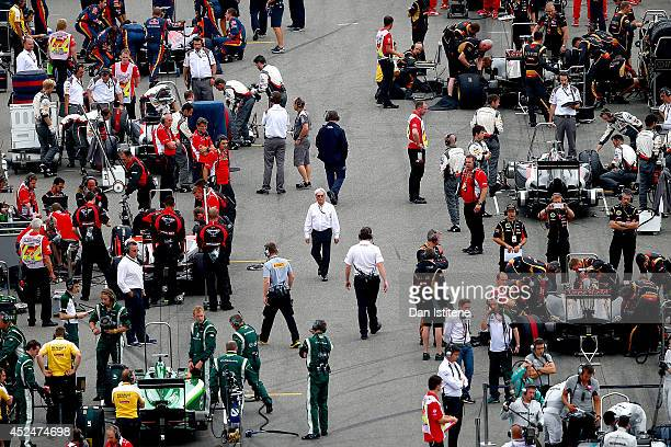 F1 supremo Bernie Ecclestone walks in between the cars as he makes his way through the grid before the German Grand Prix at Hockenheimring on July 20...