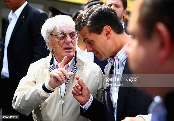 F1 supremo Bernie Ecclestone walks with the President of Mexico Enrique Pena Nieto in the pit lane during previews to the Formula One Grand Prix of...
