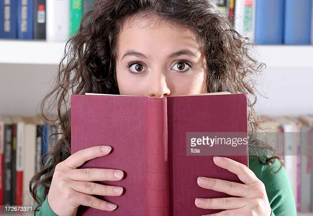 suprised girl is hidden behind a book