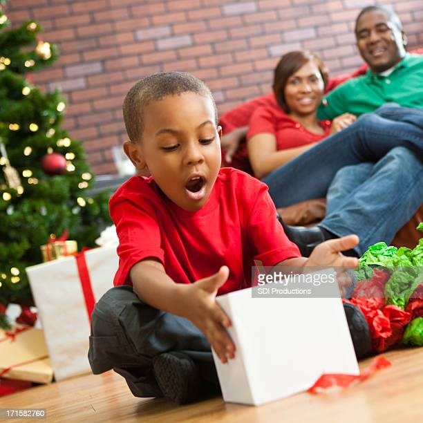 Suprised little boy opening present on Christmas morning