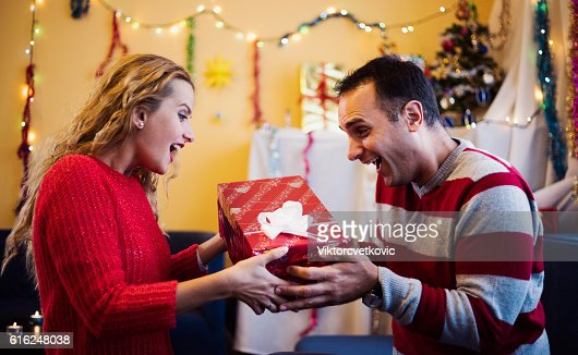 Suprised woman taking a gift from husband. Happy New Year. : Foto de stock