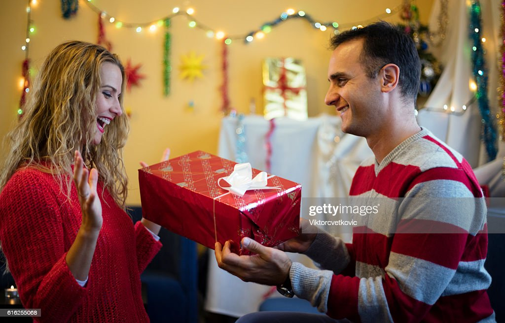 Suprised woman taking a gift from husband. Happy New Year. : Stock Photo