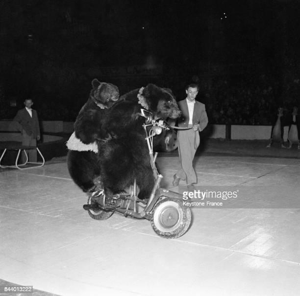 Sur la piste deux ours font de la patinette à moteur à l'occasion de l'arbre de Noël de la Préfecture de Paris au Palais des Sports à Paris France le...