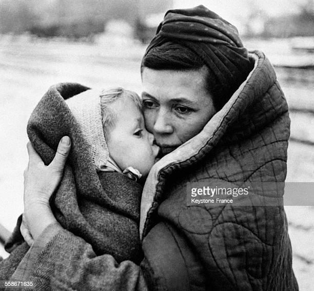 Sur le quai d'une gare une femme tient dans ses bras son enfant en attendant un train en Allemagne le 17 décembre 1945