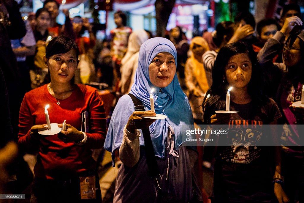 Surabaya residents pray for victims of the AirAsia flight QZ8501 crash on December 31 2014 in Surabaya Indonesia A massive recovery operation has...