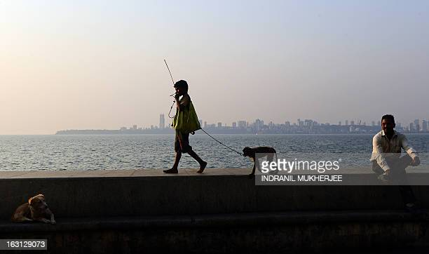 Suraj walks with his pet monkey towards a group of tourists to start a show on the Marine Drive promenade which overlooks the Arabian Sea in Mumbai...