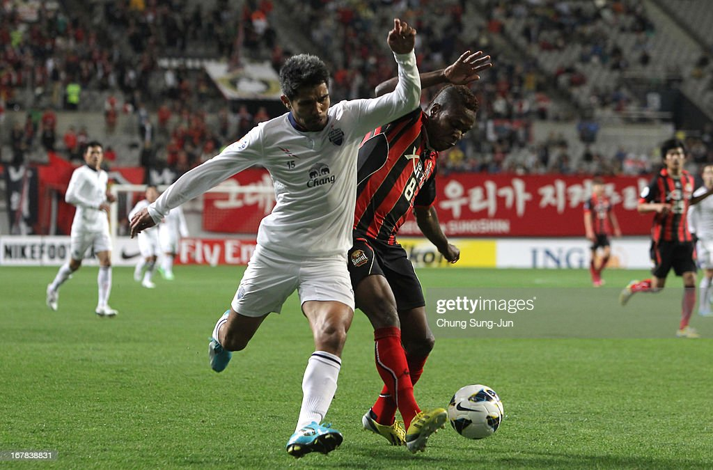 Surat Sukha of Buriram United tussles for possession with Adilson Dos Santos of FC Seoul during the AFC Champions League Group E match between FC Seoul and Buriram United at Seoul World Cup Stadium on May 1, 2013 in Seoul, South Korea.