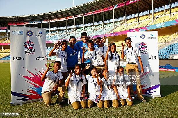 Suresh Raina and Jasprit Bumrah of India pose for the cameras with local kids during the ICC Cricket For Good and Team Swachh cricket clinics in...