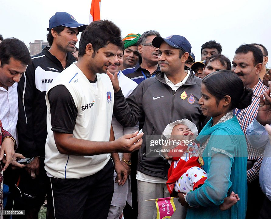 Suresh Raina, Mohammad Kaif and Virender Sehwag administerinrg polio-drops to infants at Gandhi Nagar cricket stadium during Ranji Trophy match being played between teams of Delhi and UP, on November 3, 2012 in Ghaziabad, India.