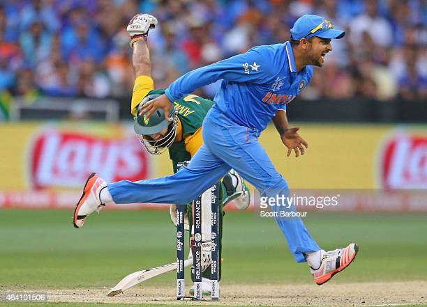 Suresh Raina of India attempts unsuccessfully to run out Hashim Amla of South Africa bats during the 2015 ICC Cricket World Cup match between South...