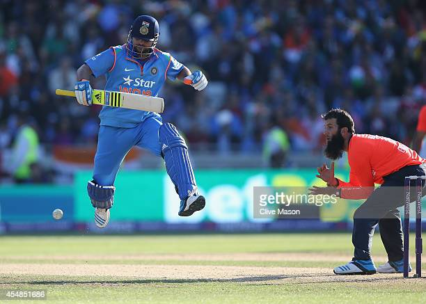Suresh Raina of India jumps to avoid a thrown ball as Moeen Ali of England looks on during the NatWest International T20 2014 match between England...