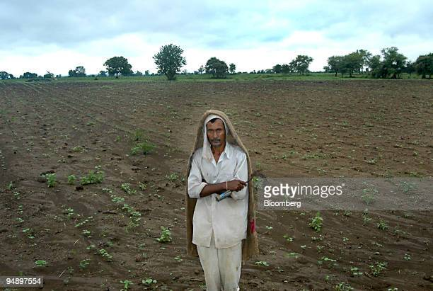 Suresh Rao Meshram stands in the field of his failed cotton crop August 1 2004 and plans to hire himself out as a hired laborer in a nearby village...