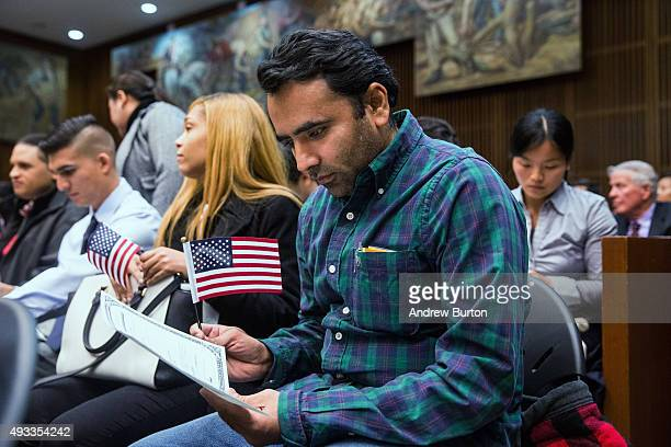 Sureshbhai Shambhubhai Patel a new US citizen looks at his certficate of citizenship at the end of his naturalization ceremony at the United States...