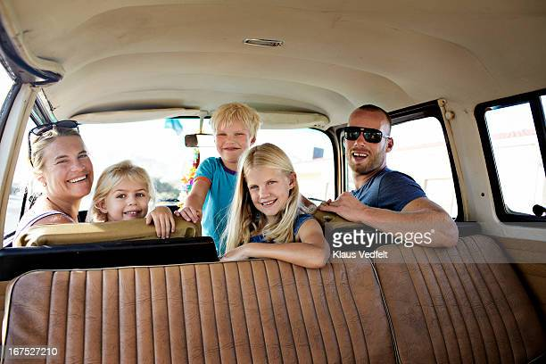 Surf family hanging out in their old car