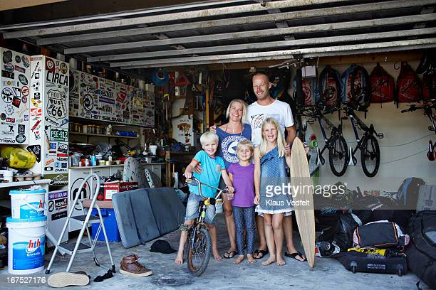 Surf family standing in their garage
