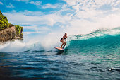 Surf girl on surfboard. Woman in ocean during surfing. Surfer and ocean wave