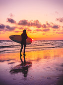 Surf girl with surfboard with warm sunset or sunrise colors