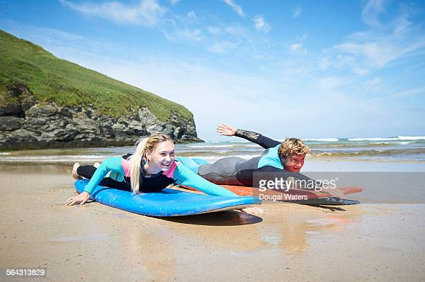 Surf instructor and woman practicing on beach