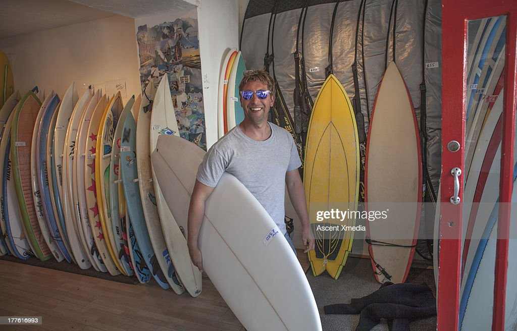 Surf shop employee carries surfboard out to surf : Stock Photo