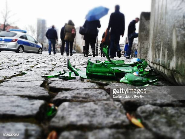 Surface level of a broken bottle with people walking on street