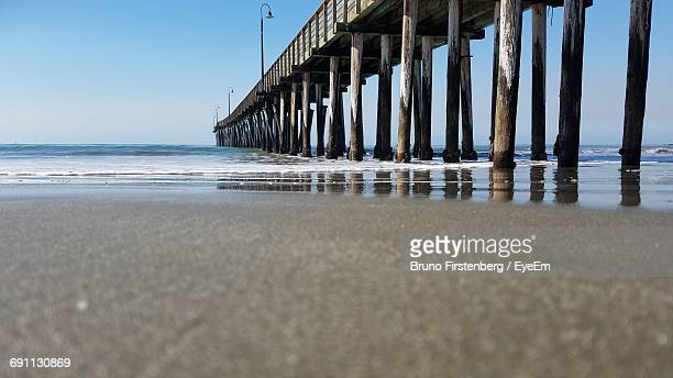 Surface Level Of Beach With Pier Against Clear Sky