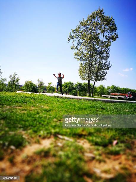 Surface Level Of Boy Jumping On Field Against Sky