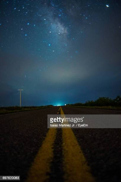 Surface Level Of Empty Road Against Star Field In Blue Sky At Night