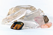 Eye level close up of  quartz crystals and tiger's eye stone on white. Not isolated