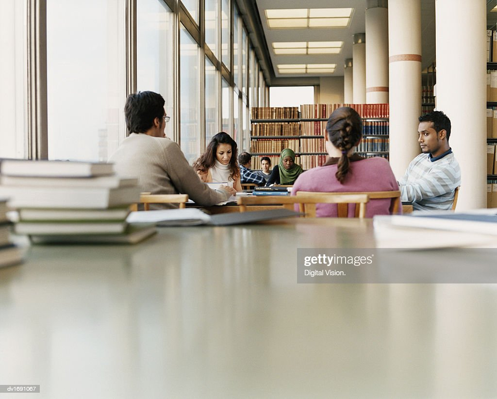 Surface Level Shot of Mature Students Sitting at a Table in a University Library : Stock Photo