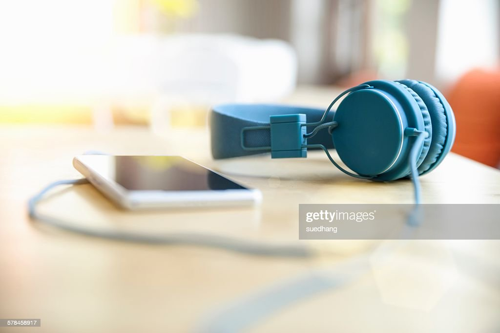 Surface level view of blue headphones attached to smartphone on table
