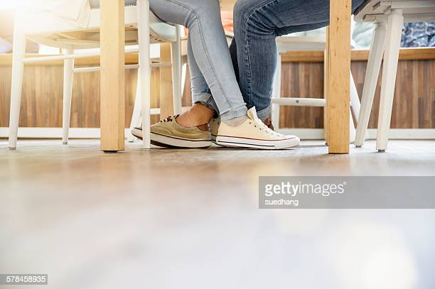 Surface level view of couples entwined legs sitting at table face to face