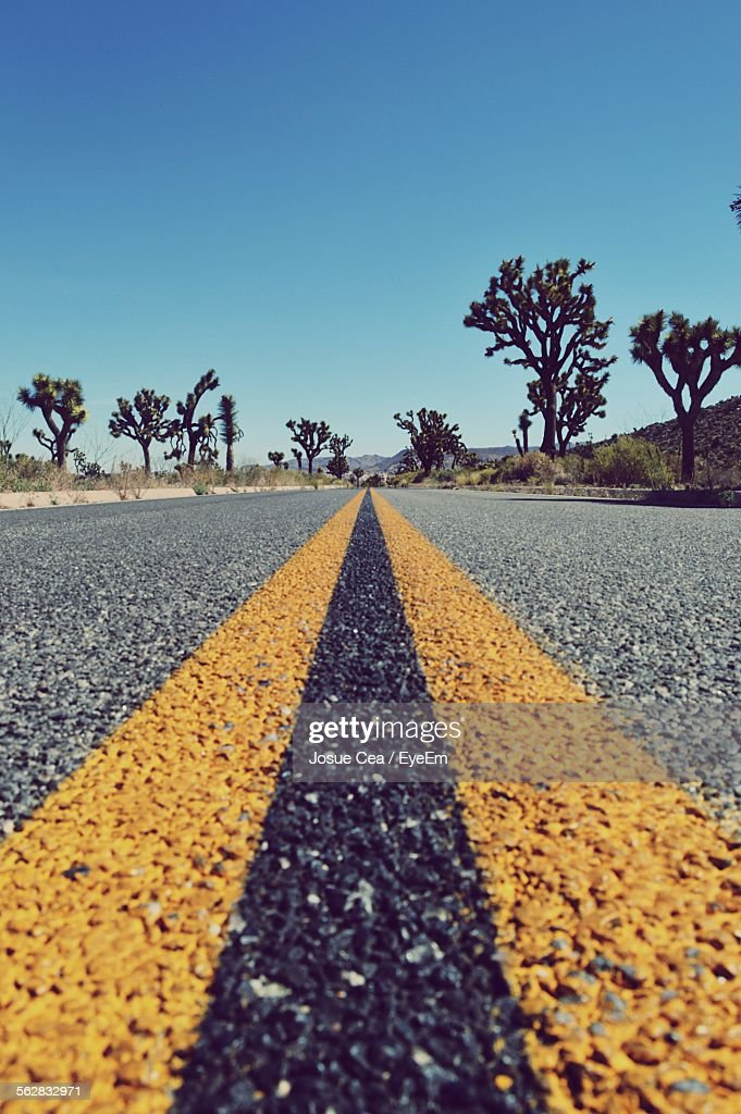 Surface Level View Of Double Yellow Line Highway Against Clear Sky
