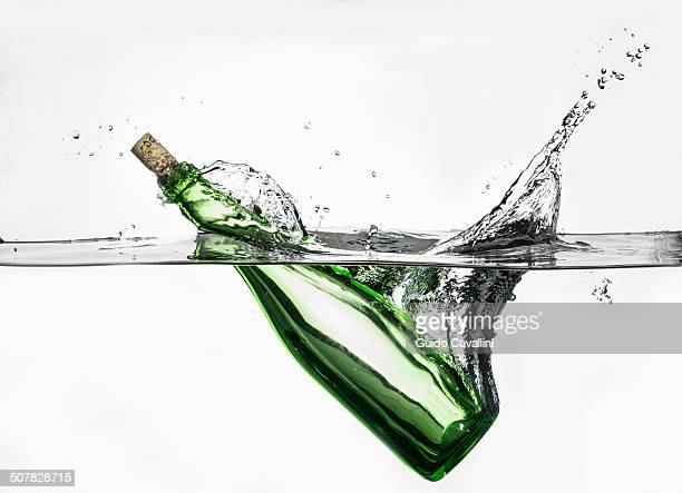 Surface level view of green bottle splashing into clear water