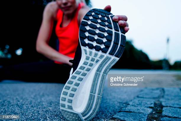 Surface level view of woman training, touching sole of training shoe in park at dusk