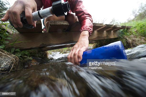 Surface view of female hiker with water filter filling water bottle in stream