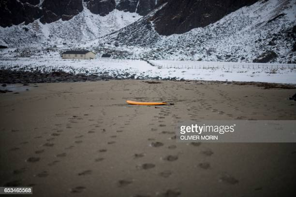 A surfboard is left on the sandy beach at Unstad along the northern Atlantic Ocean on March 12 where the water temperatures is at five degrees...