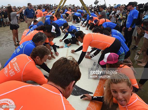 A surfboard is waxed as sixty six surfers from Huntington Beach prepare to break the 'Guinness Book of Records' record for the largest number of...