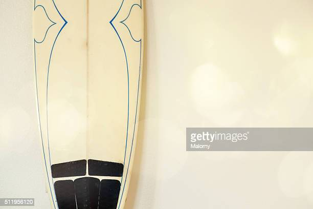 Surfboard, leaning on the wall, no people.