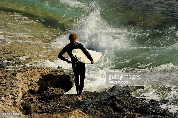 A surfboard rider prepares to enter the water at the Margaret River break in the worldrenowned surfing area of the southwest corner of Western...