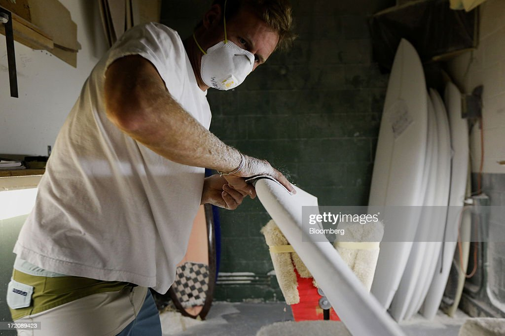 Surfboard shaper James Wheatley shapes a foam blank board into a Becker Surfboard at the Mangiagli Manufacturing facility in Hermosa Beach, California, U.S., on Monday, July 1, 2013. The U.S. Census Bureau is scheduled to release factory orders figures on July 2. Photographer: Patrick T. Fallon/Bloomberg via Getty Images