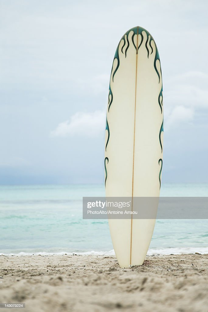 Surfboard stuck in sand at the beach : Stock Photo