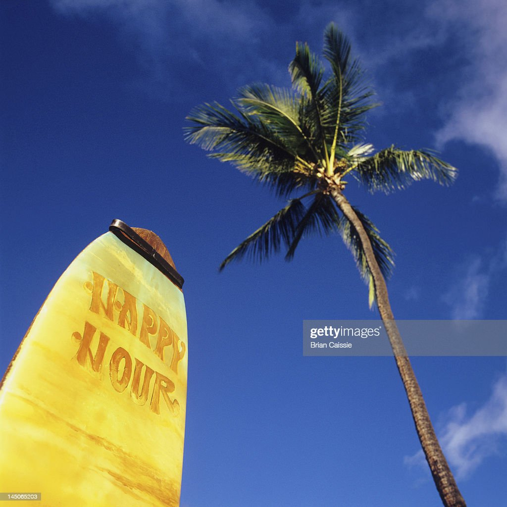 A surfboard with Happy Hour on it and a palm tree