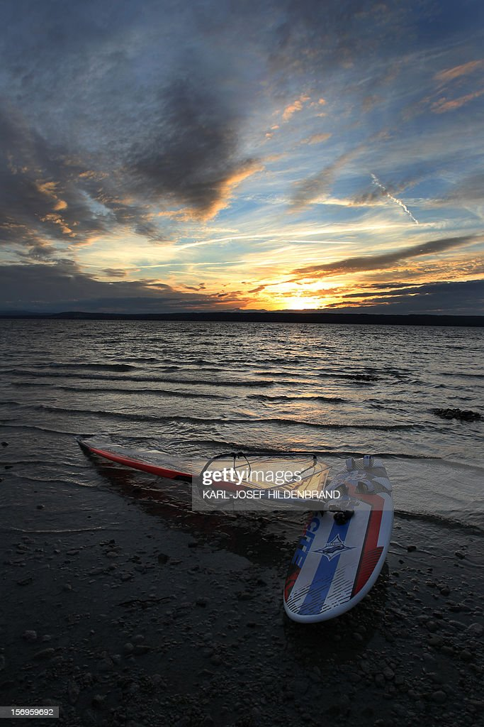Surfboard with sail lies on the shore at the Ammer lake near Herrsching, southern Germany, on November 25, 2012. AFP Photo / Karl-Josef Hildenbrand /GERMANY OUT