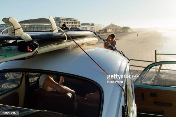 Surfboards on car roof, couple kissing in background