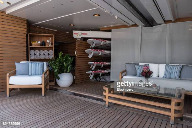 Surfboards sit in a rack behind lounge seating on the desk of luxury yacht Latitude manufactured by Benetti SpA during the Monaco Yacht Show in Port...