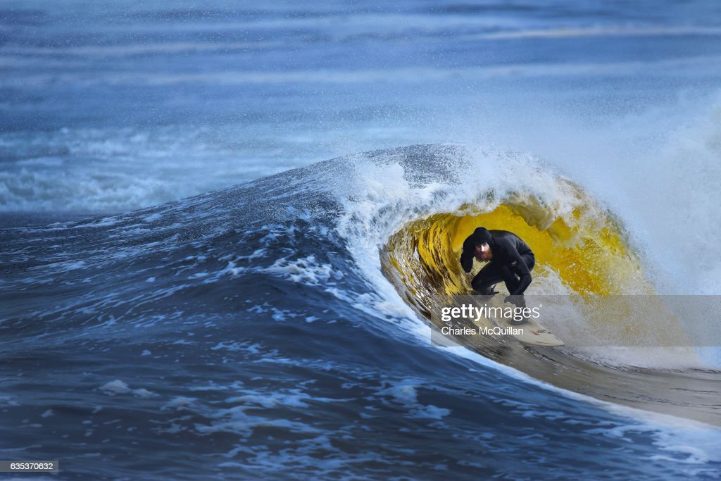 Surfer Al Mennie catches a golden barrel on January 12, 2017 in Portballintrae, Northern Ireland. The position of the turf rich River Bush which runs past the famous Bushmills whiskey distillery, provides a distinctive colouring as it meets the north Atlantic waters of Portballintrae.