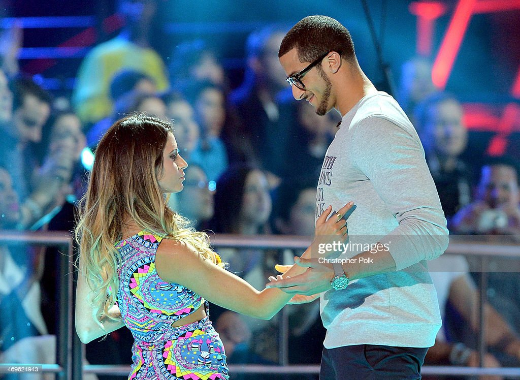 Surfer Anastasia Ashley (L) and co-host Colin Kaepernick speak onstage during Cartoon Network's fourth annual Hall of Game Awards at Barker Hangar on February 15, 2014 in Santa Monica, California.