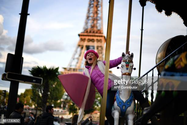 US surfer and adventurer Alison Teal poses with her surf on a merrygoround in Paris on September 19 2017 After tackling wastewater in Mexico and a...